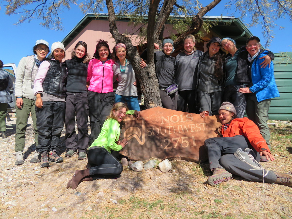 Group of women smiles in front of the NOLS Southwest address marker