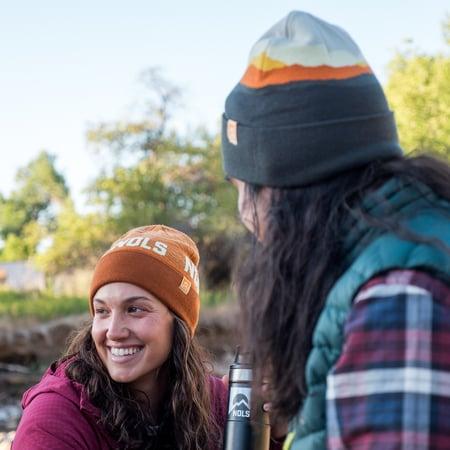 Two people wearing beanies smile