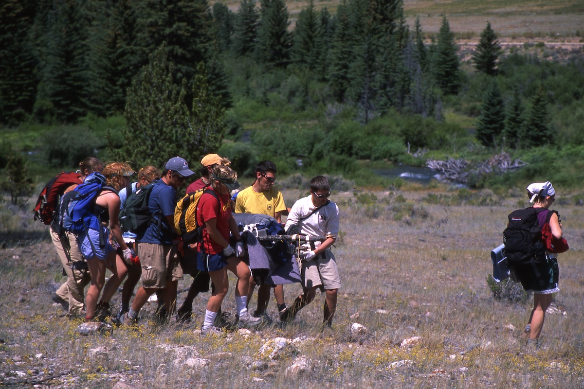 Archival photo from the 90s of a group carrying a litter in a rocky field