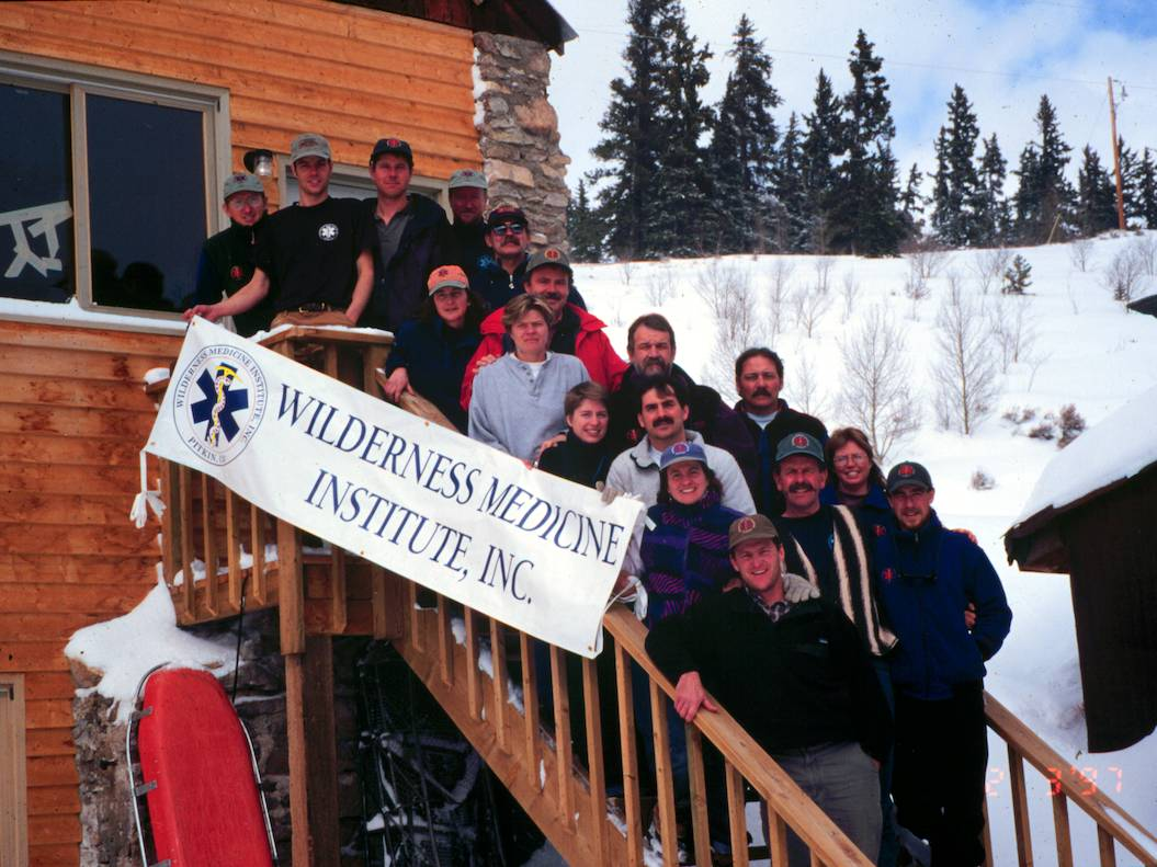 "Group picture of staff in front of the early WMI Staff Building holding a banner that says ""Wilderness Medicine Institute, Inc."""
