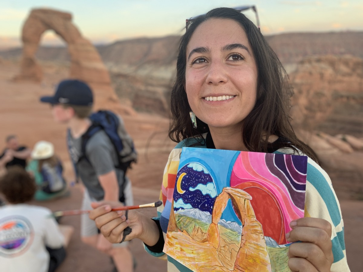Artist smiles and holds up a painting of redrock arch