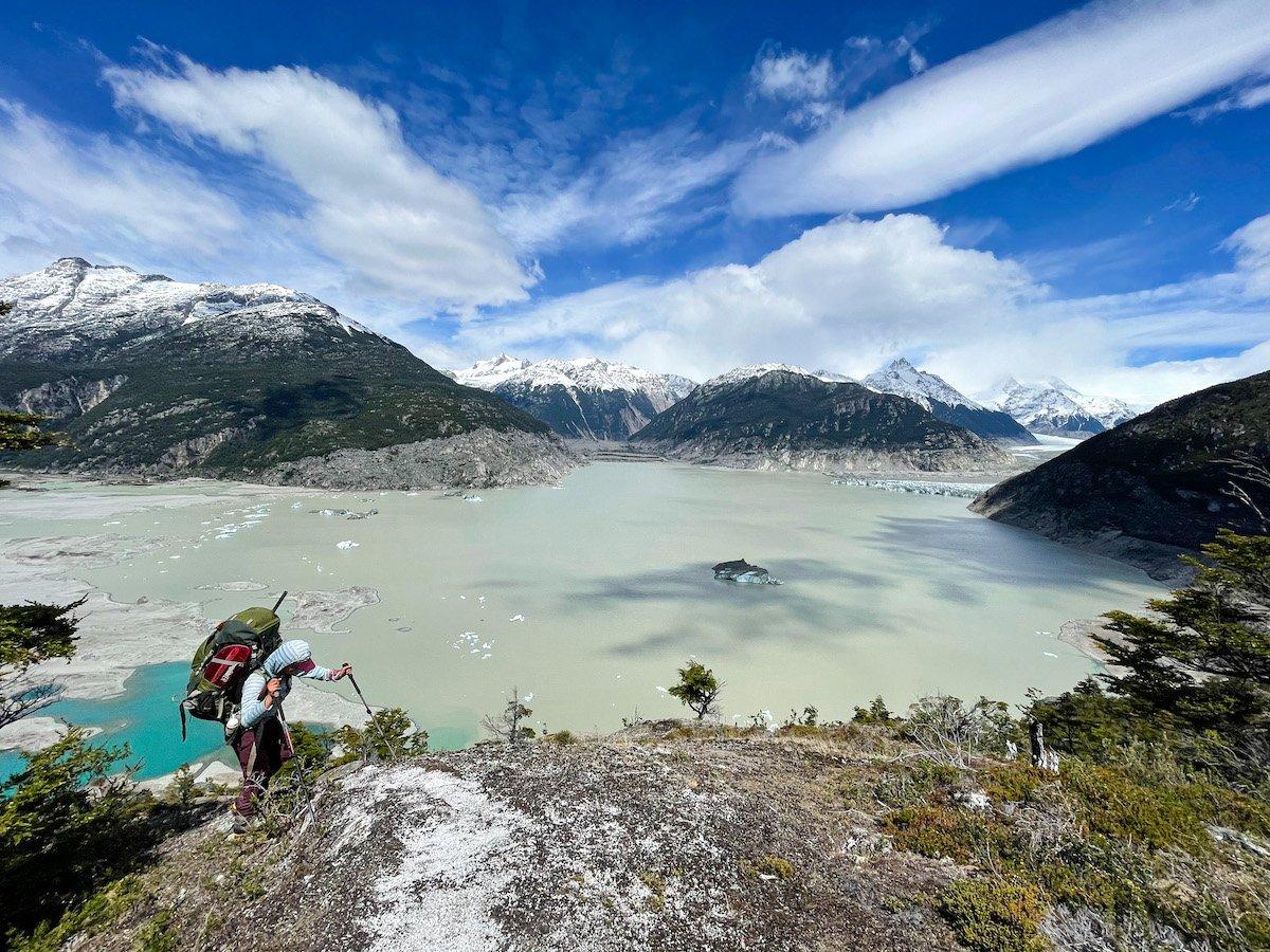 Woman hikes above a large mountain lake