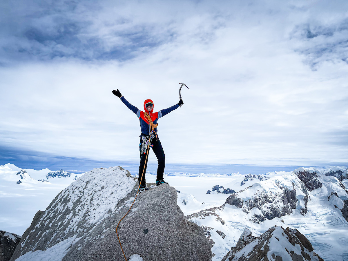 Woman stands on the summit and lifts her arms in celebration