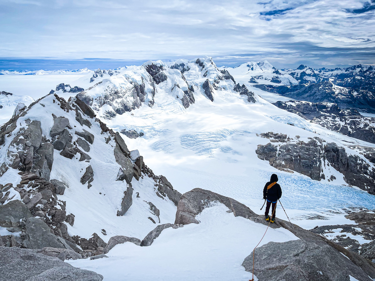 Mountaineer overlooks the descent with a large glacier below