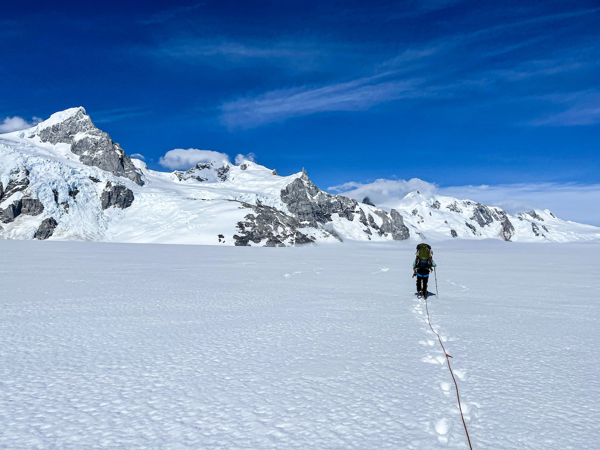 Woman crosses a large snow-covered glacier