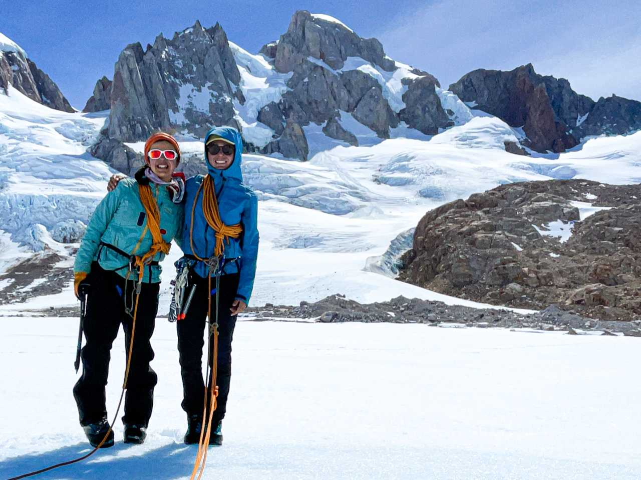 Two women smile while set up for glacier travel in front of Patagonian peaks