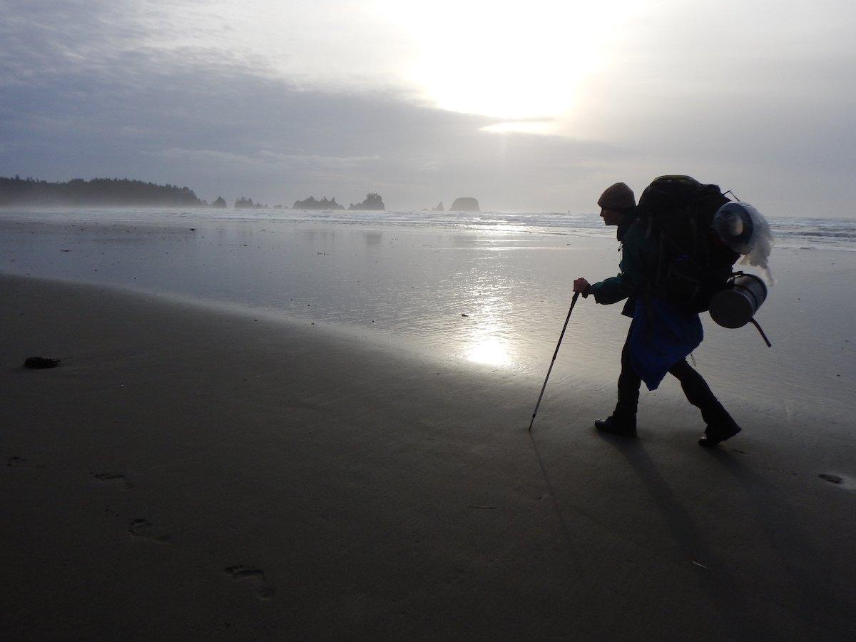 Silhouette of author hiking on a foggy coastline