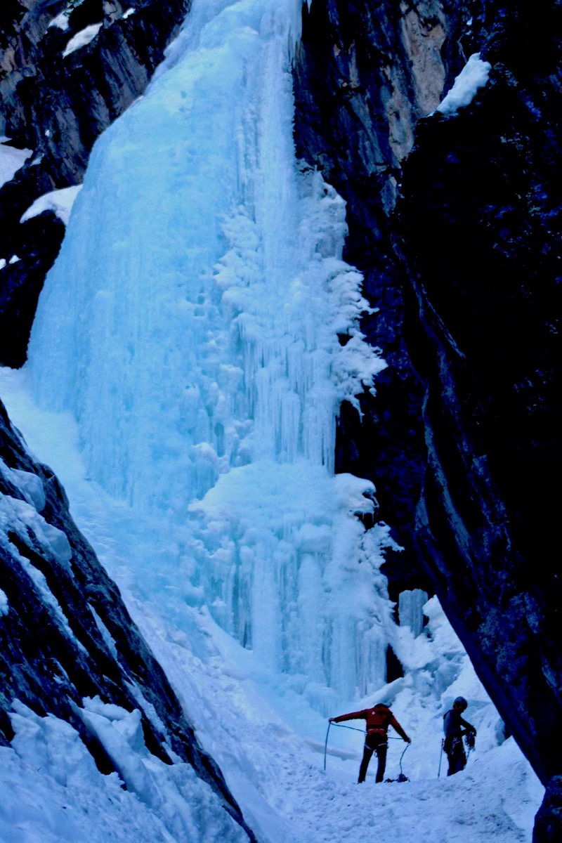 Two climbers coil a rope at the base of an ice waterfall