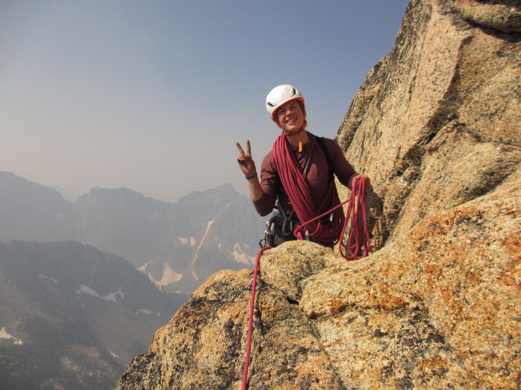 Climber smiles and shows a peace sign while coiling rope partway up an alpine climb