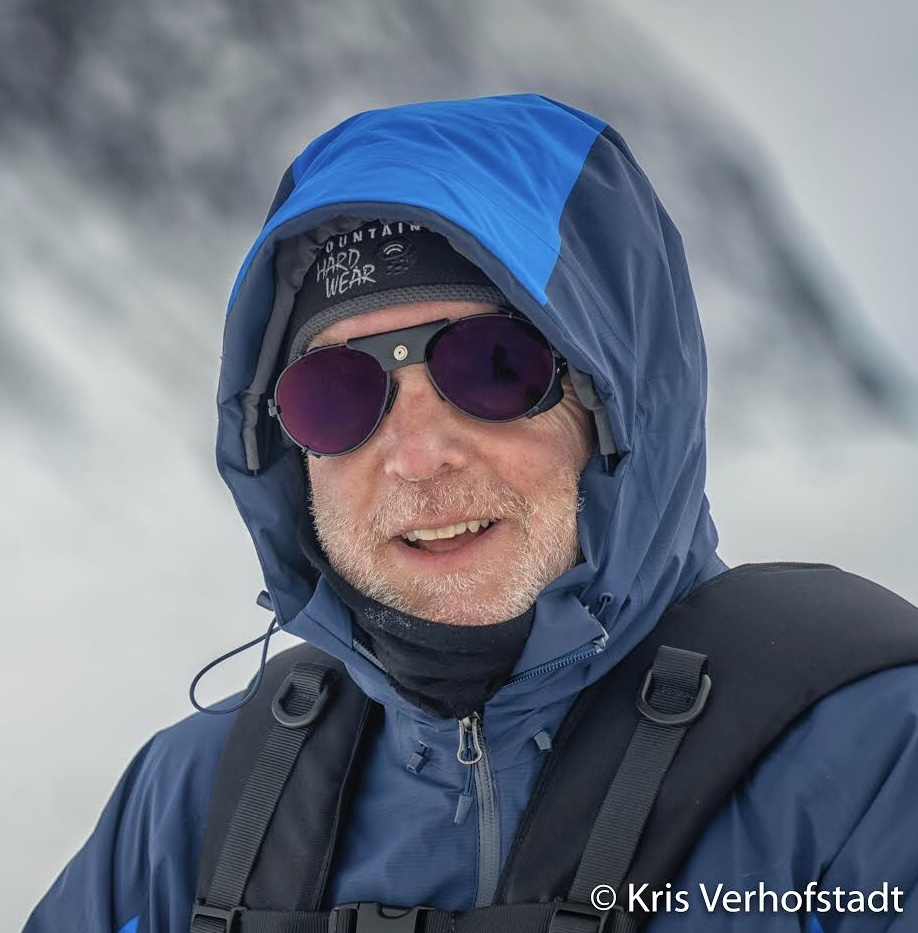 Close up of Eric wearing sunglasses and a hooded jacket for hiking