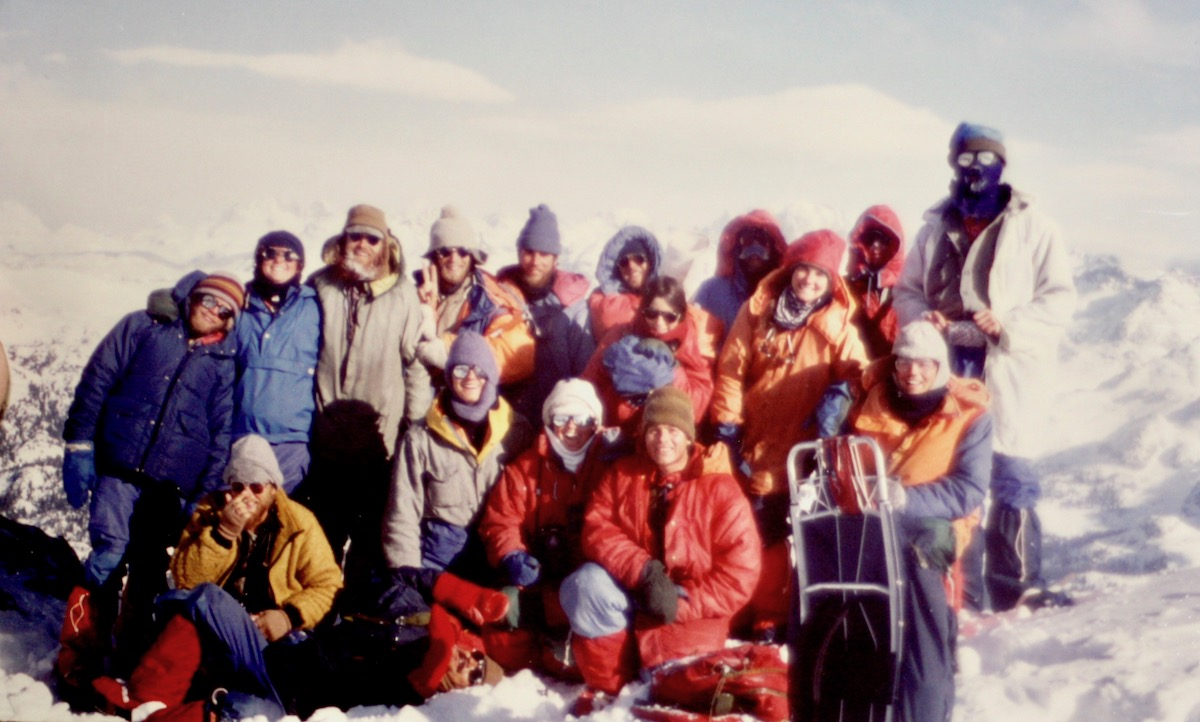Archival photo of large smiling NOLS group on a mountaineering course