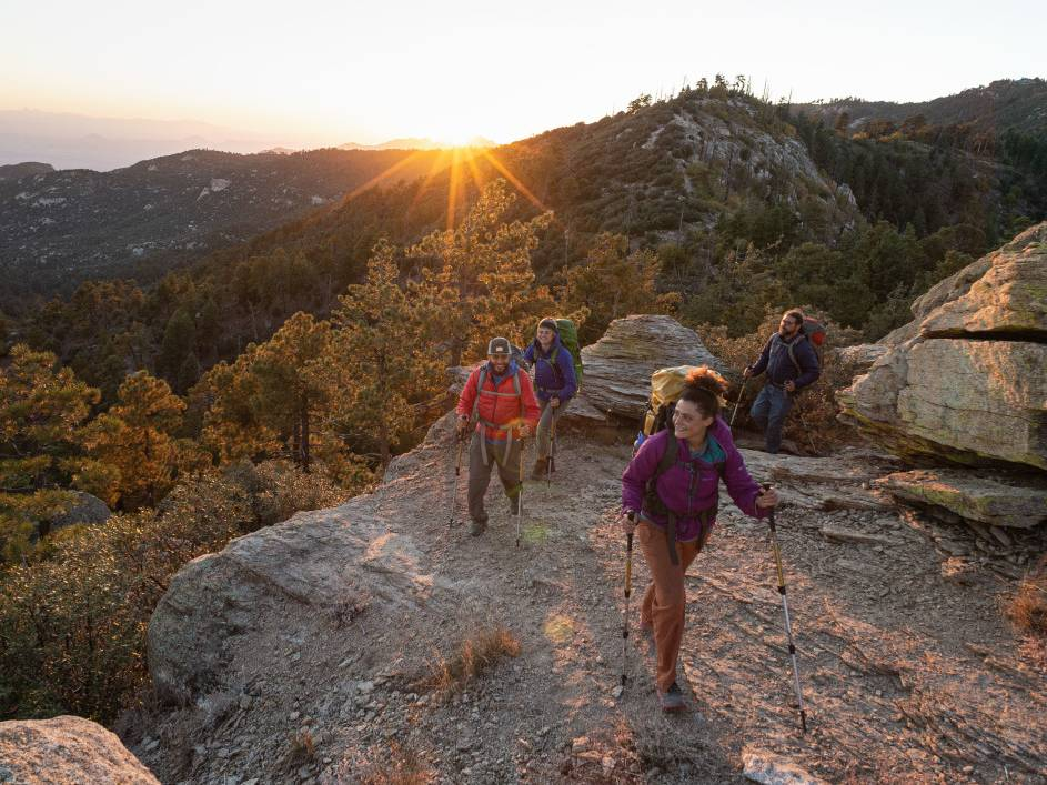 Three backpackers ascend a ridge
