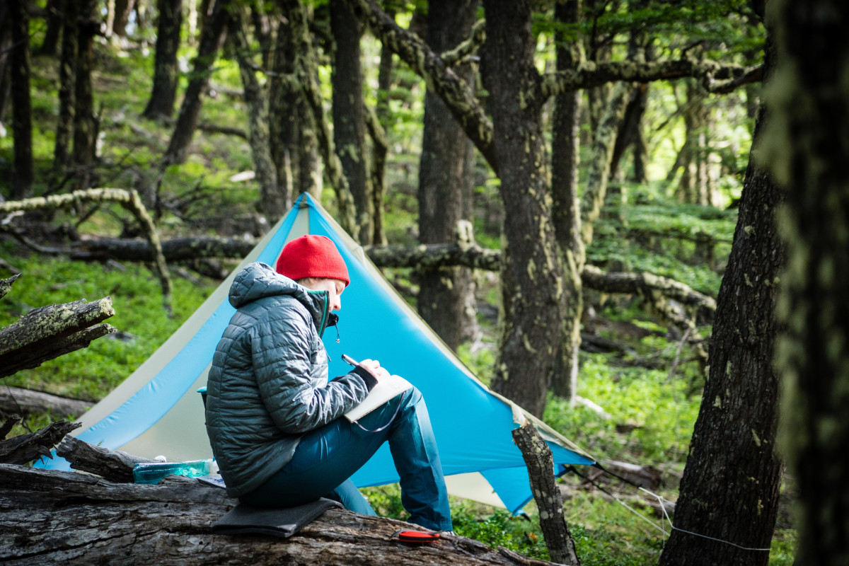 Man writes in a journal in front of his tent in the forest
