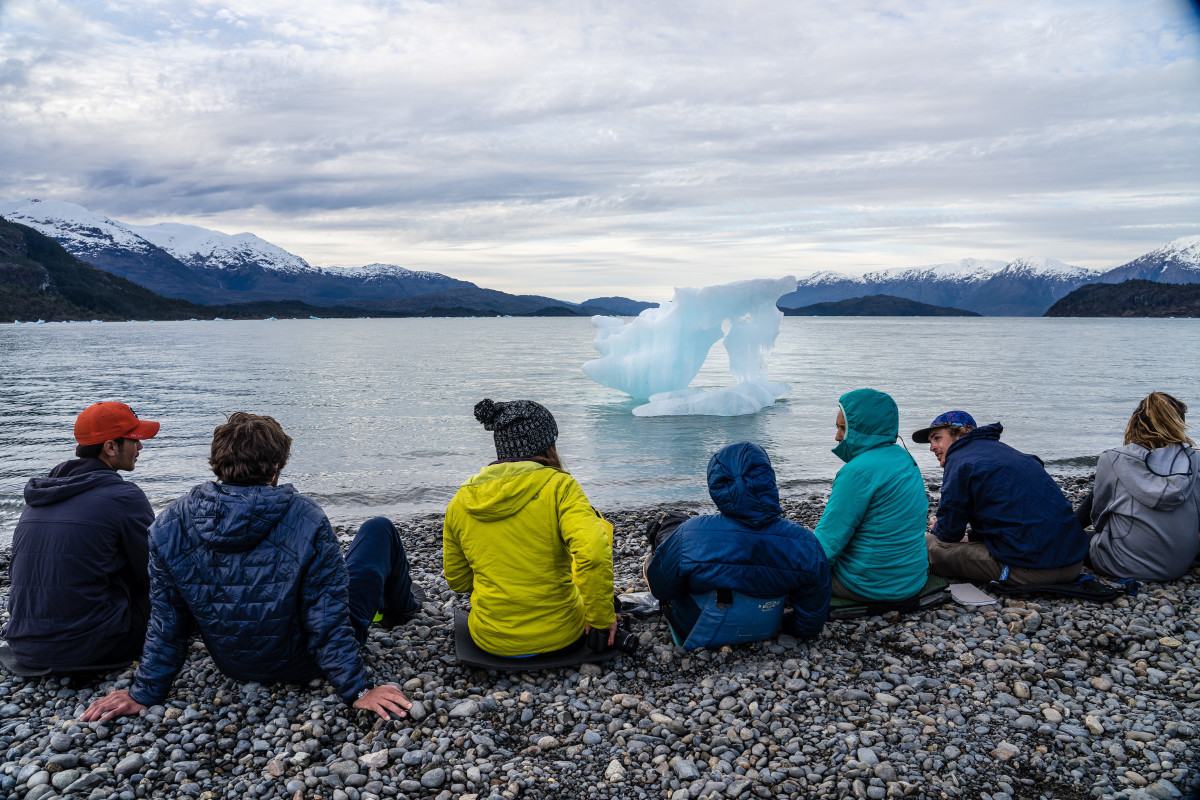 NOLS students sit on a rocky shore looking at a small ice floe