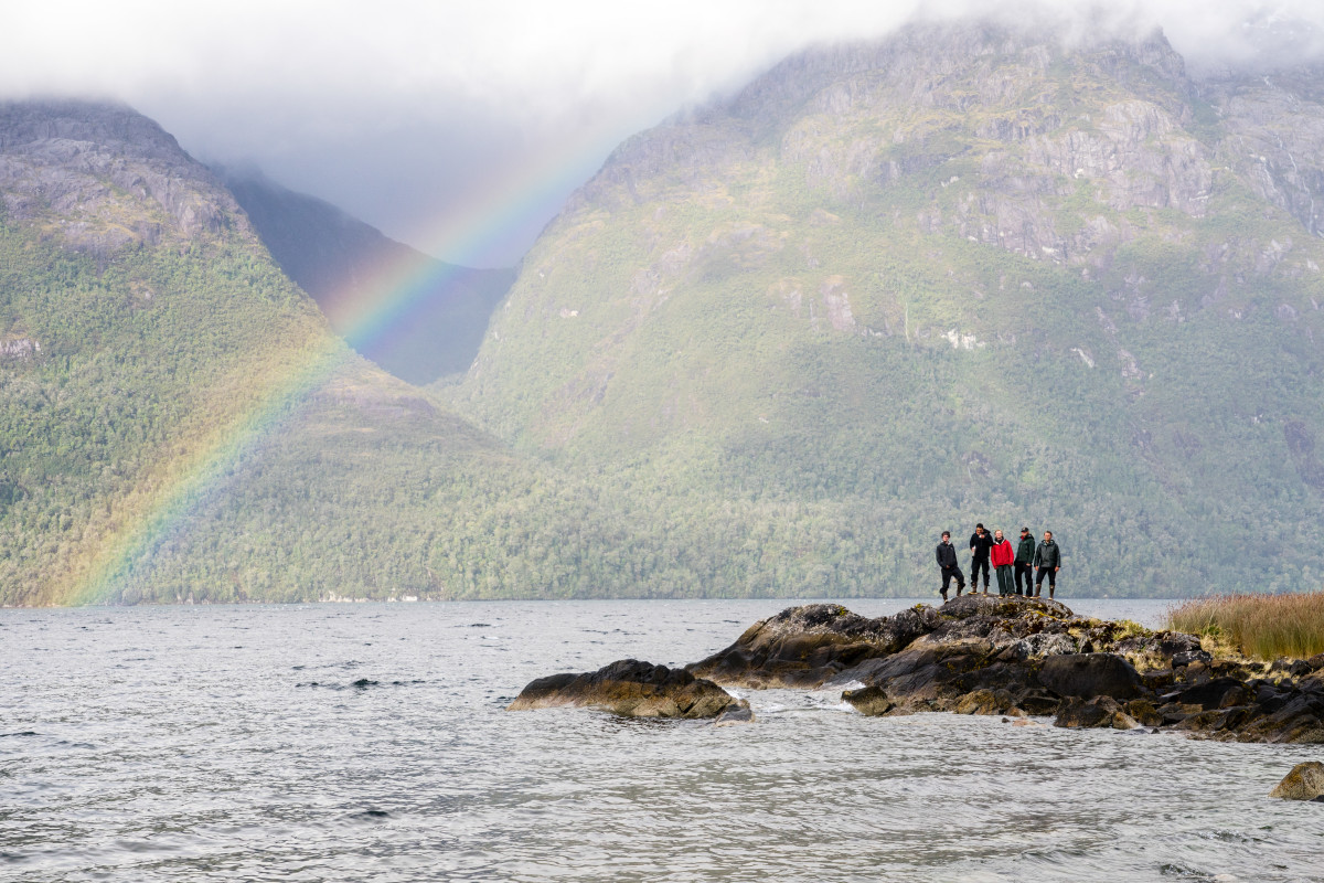Rainbow stretches across the ocean observed by a group of NOLS students on shore
