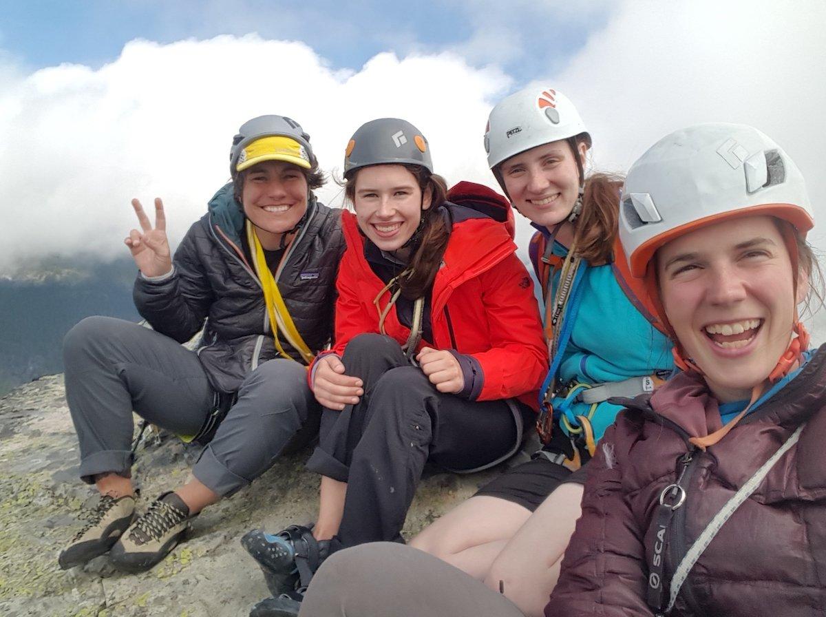 Four climbers smile wearing climbing helmets on an alpine rock summit