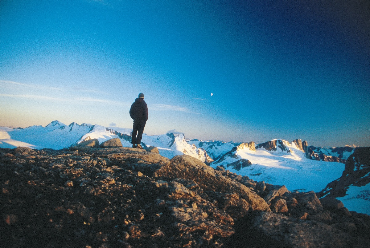 Person stands on mountaintop looking at moonrise over faraway ridges
