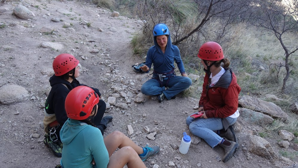 Four climbers sit together in a circle, with their helmets and gear still on, to chat.