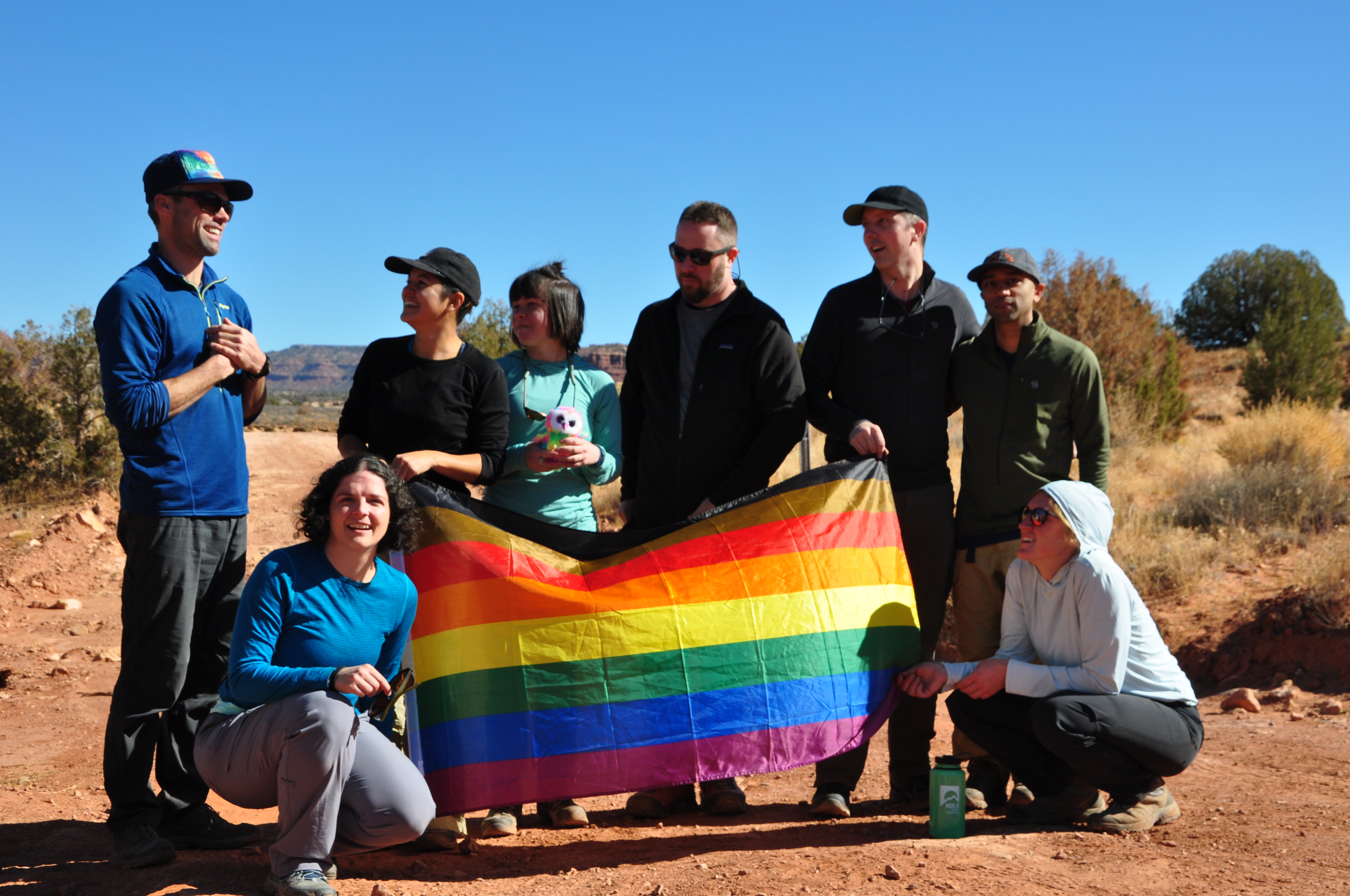 NOLS students pose for a group photo with rainbow flag in Utah's canyonlands