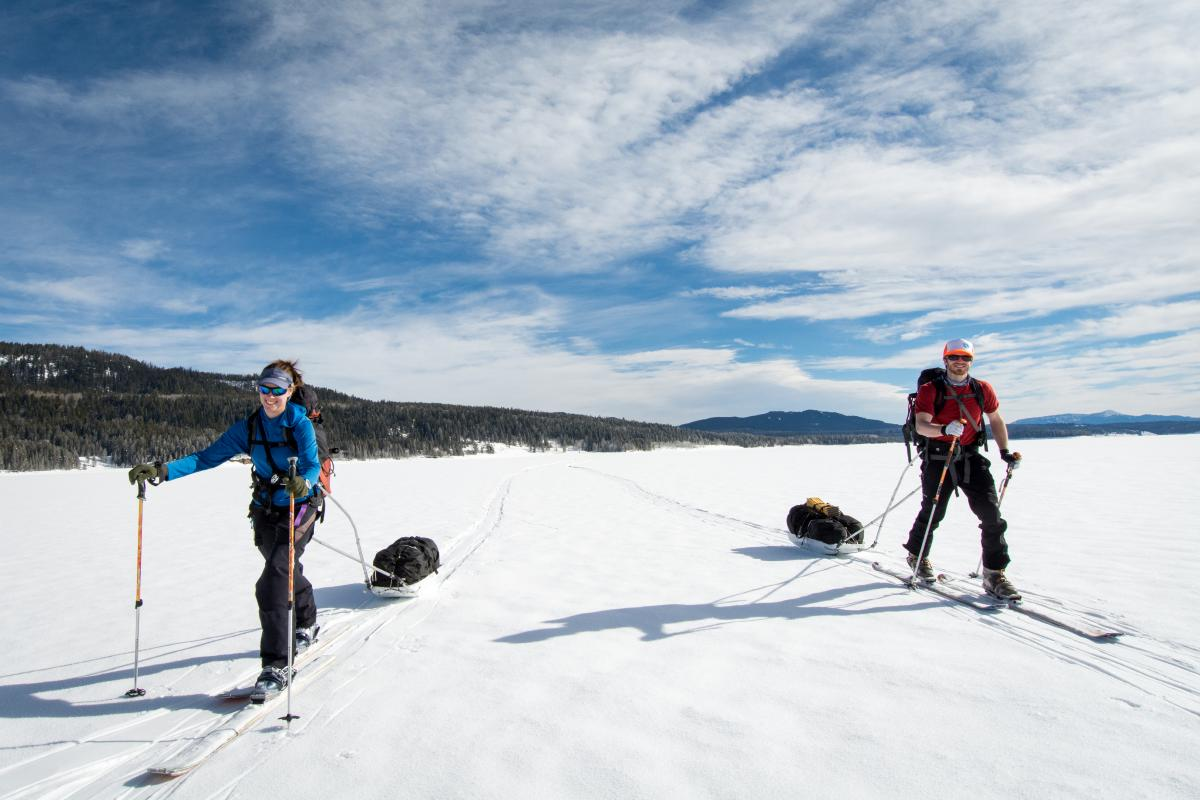 Two people ski touring across an open snow-covered meadow
