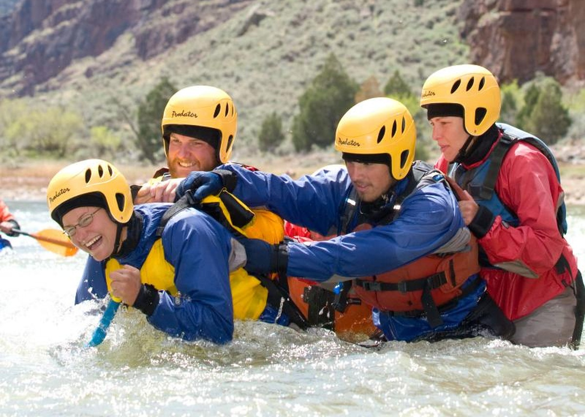 Group practices river crossing wearing helmets and lifejackets