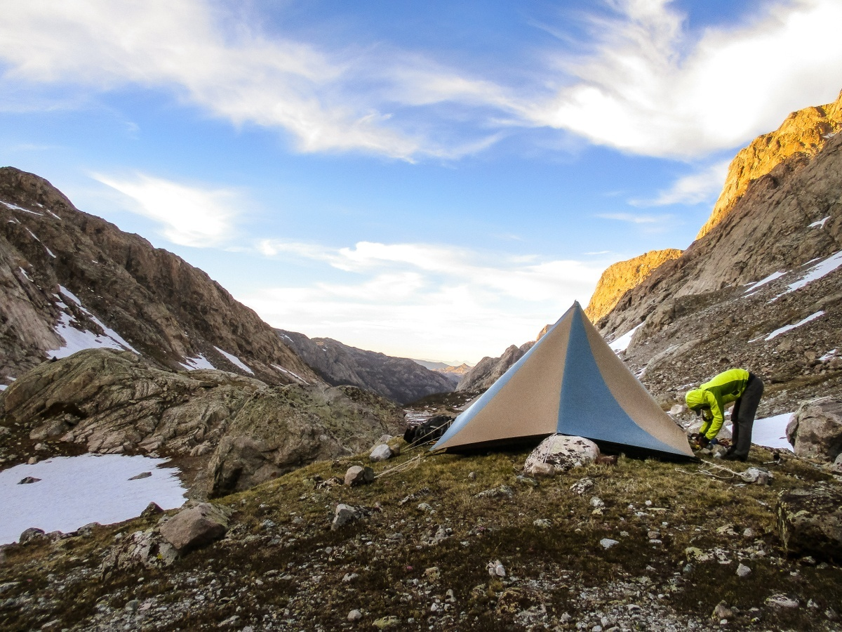 Person sets up a tent in the mountains