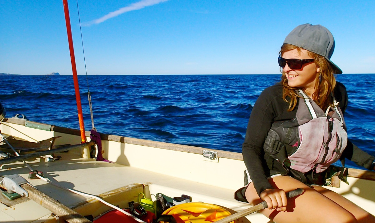 Woman wearing a hat and sunglasses sitting in a boat