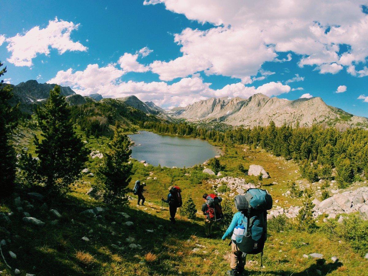 Group hikes down a hill toward an alpine lake