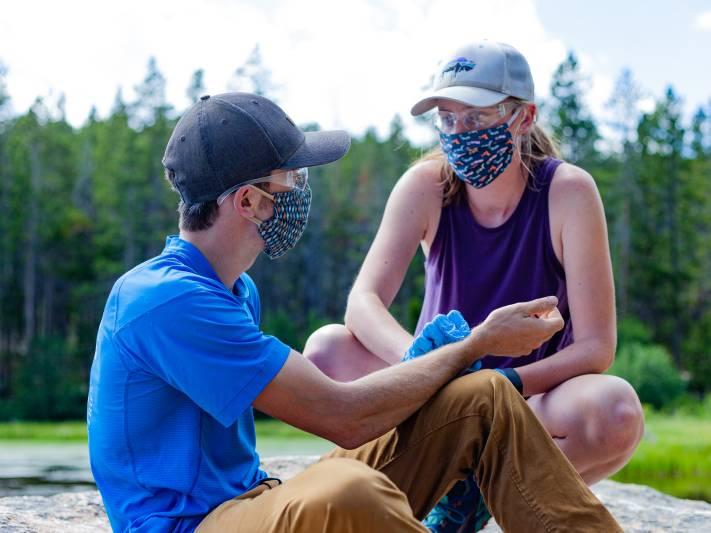 Woman takes a man's pulse during a practice scenario