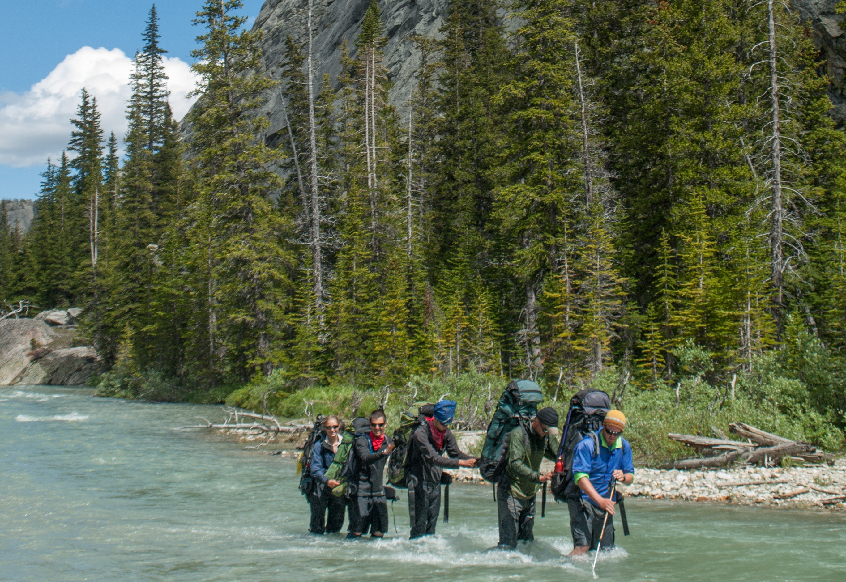 Five people wearing backpacks cross a river with pine trees on the riverbank