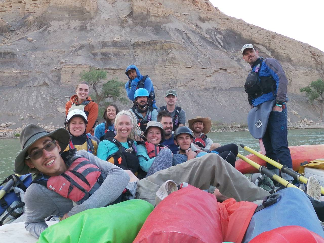 NOLS group smiles while resting on a river bank