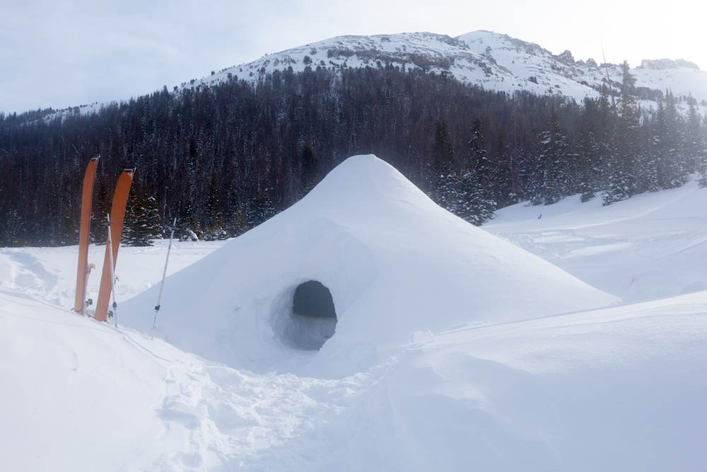 A quinzhee snow shelter stands in front of a mountain with a pair of skis outside its door.