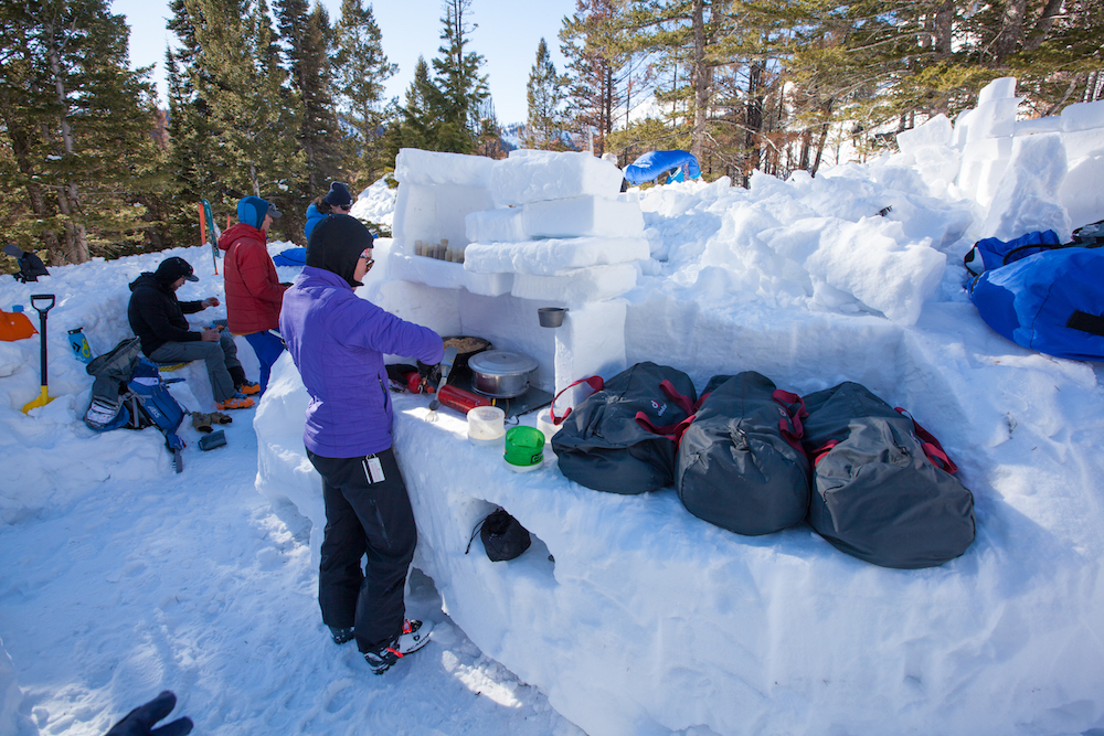 """A snow kitchen with shelves, benches, a """"stove,"""" and an icebox"""