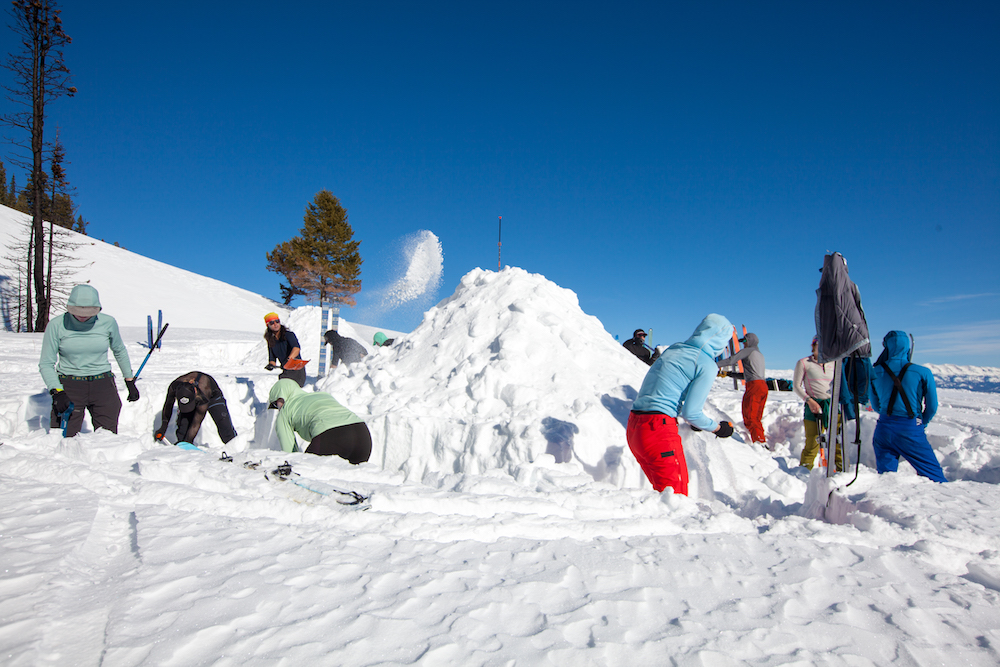 A group of winter campers shovel snow into a mound that will become a quinzhee