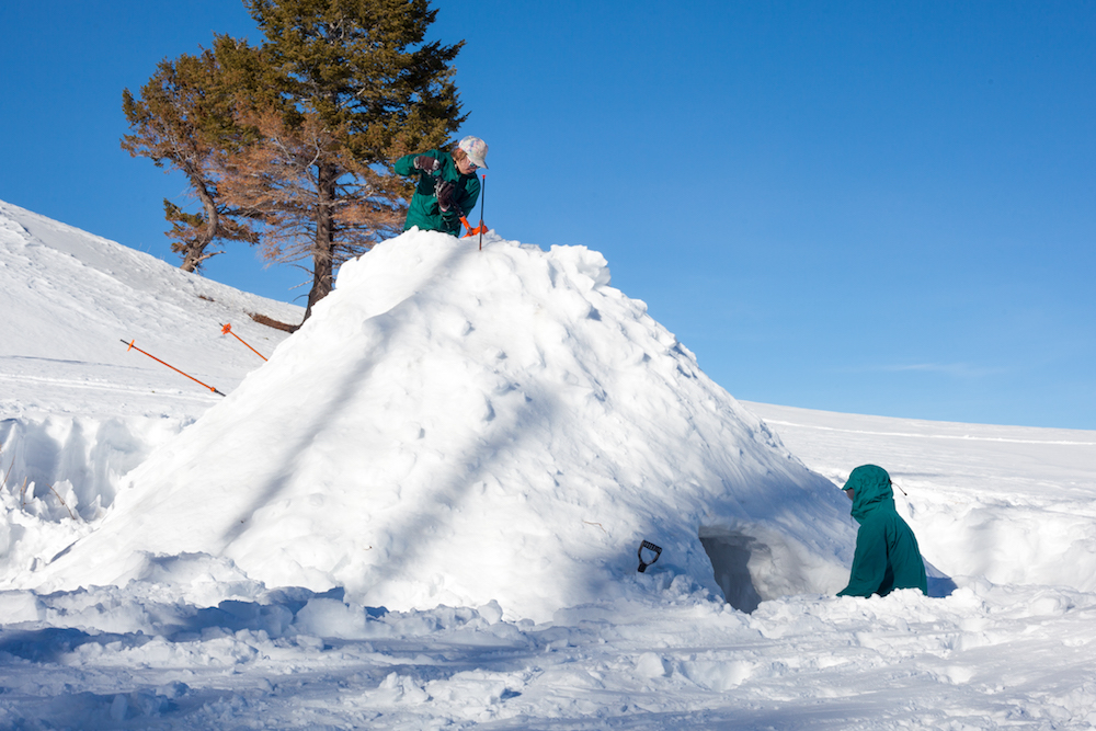 A camper climbs to the top of quinzhee to carve a vent for air