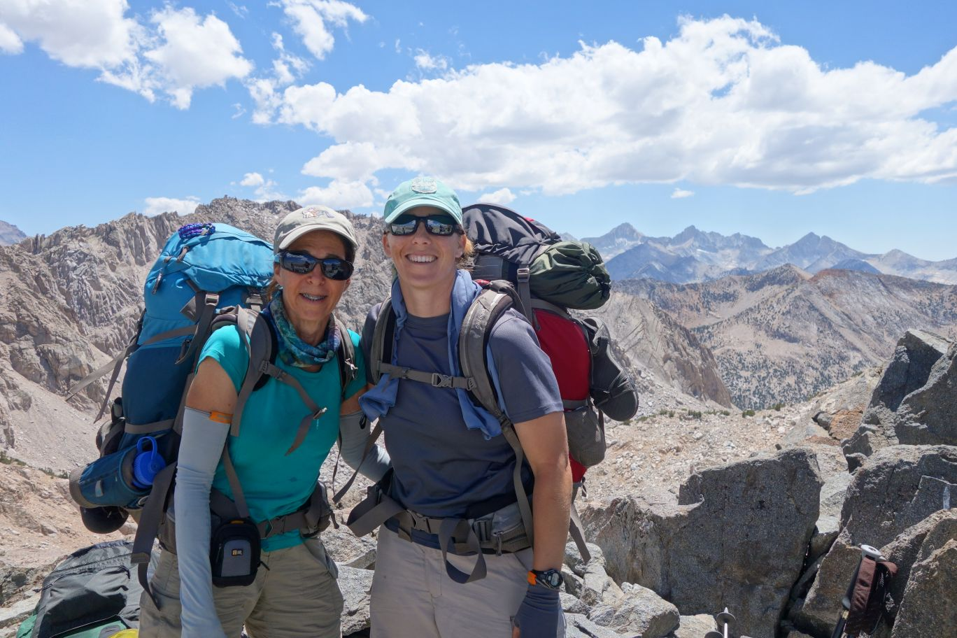 two female backpackers wearing sungasses and hats stand together high in the mountains