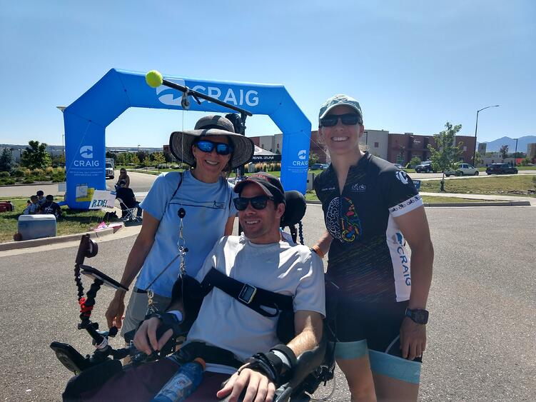 smiling family of three at the end of a bike race with daughter wearing cycling attire and son in an electronic wheelchair