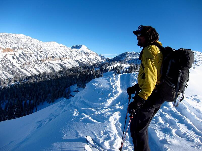 NOLS participant looks out at a snow-covered ridge while backcountry touring in the Rockies