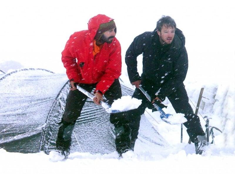 NOLS participants shovel snow outside a tent to stay warm