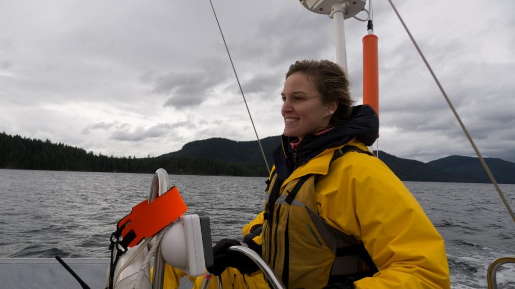 woman looking confident while steering a keelboat sailing boat in the PNW