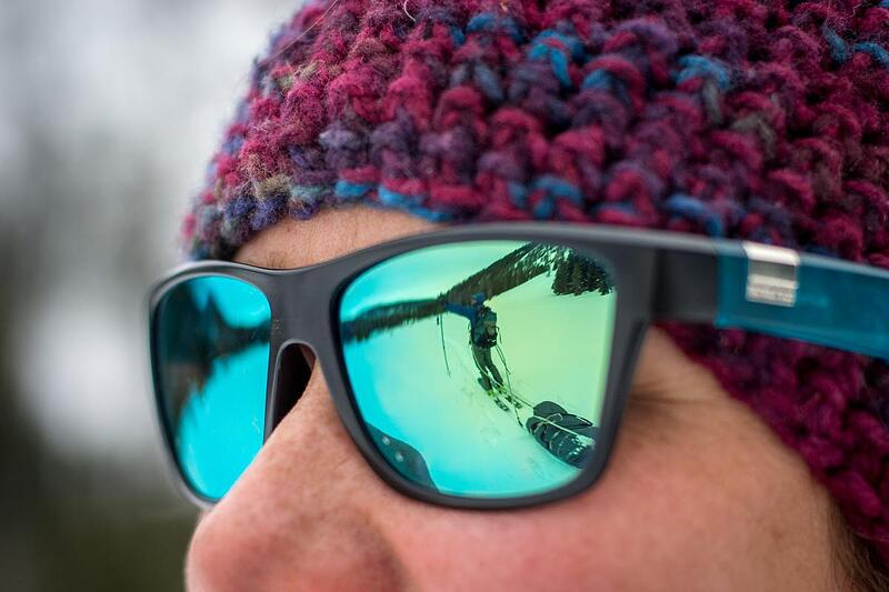 NOLS participant pulling a sled in the snow while backcountry touring is reflected in someone's sunglasses