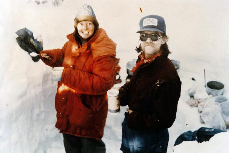 two NOLS participants on a winter course in the 1970s smile at the camera in a snow kitchene