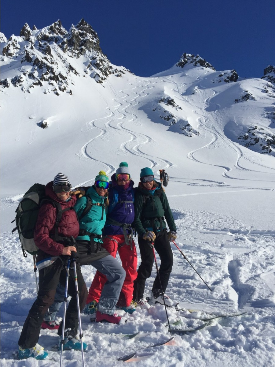 Group of 4 people smiling and wearing touring skis with mountains in the background