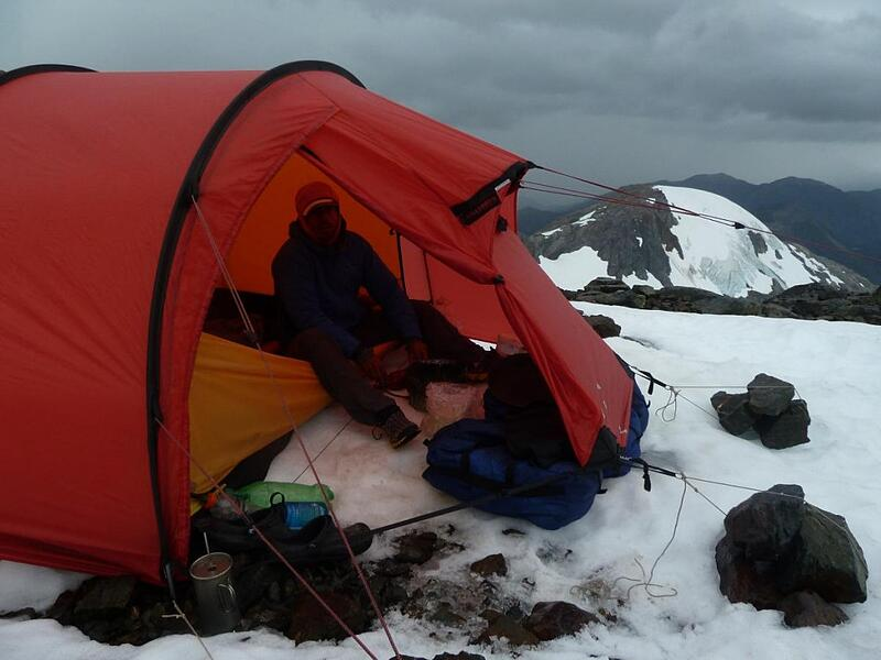 NOLS participant sits in the vestibule of tent in snowy mountains