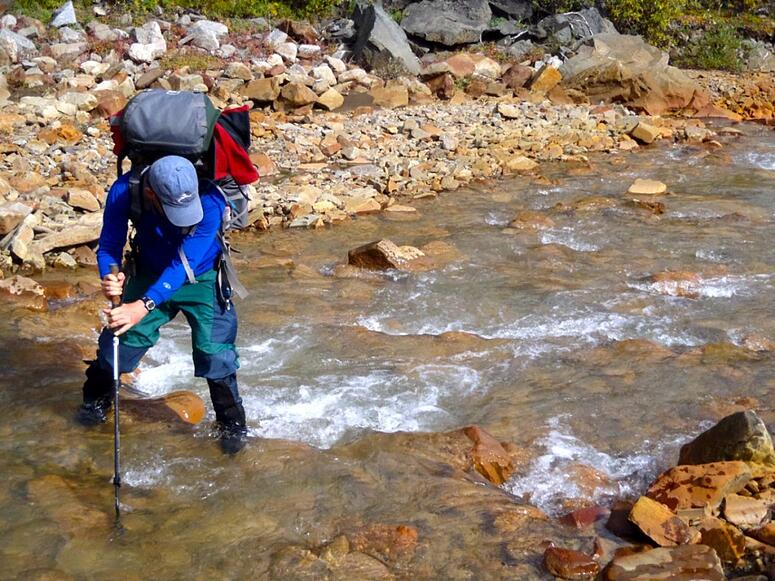 Person crossing a river using a trekking pole for balance