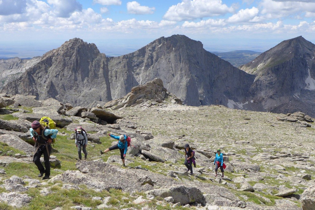 A group of five hikers go uphill with large cliffs int he background in the Wind River Range