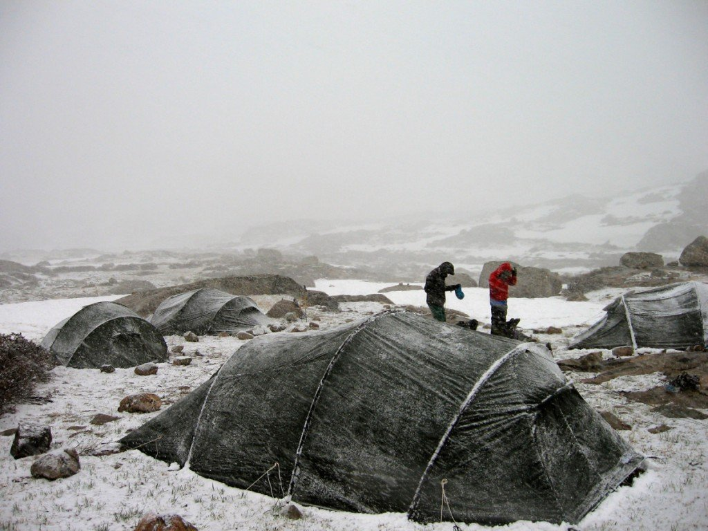Two people in a group tentsite while it's snowing