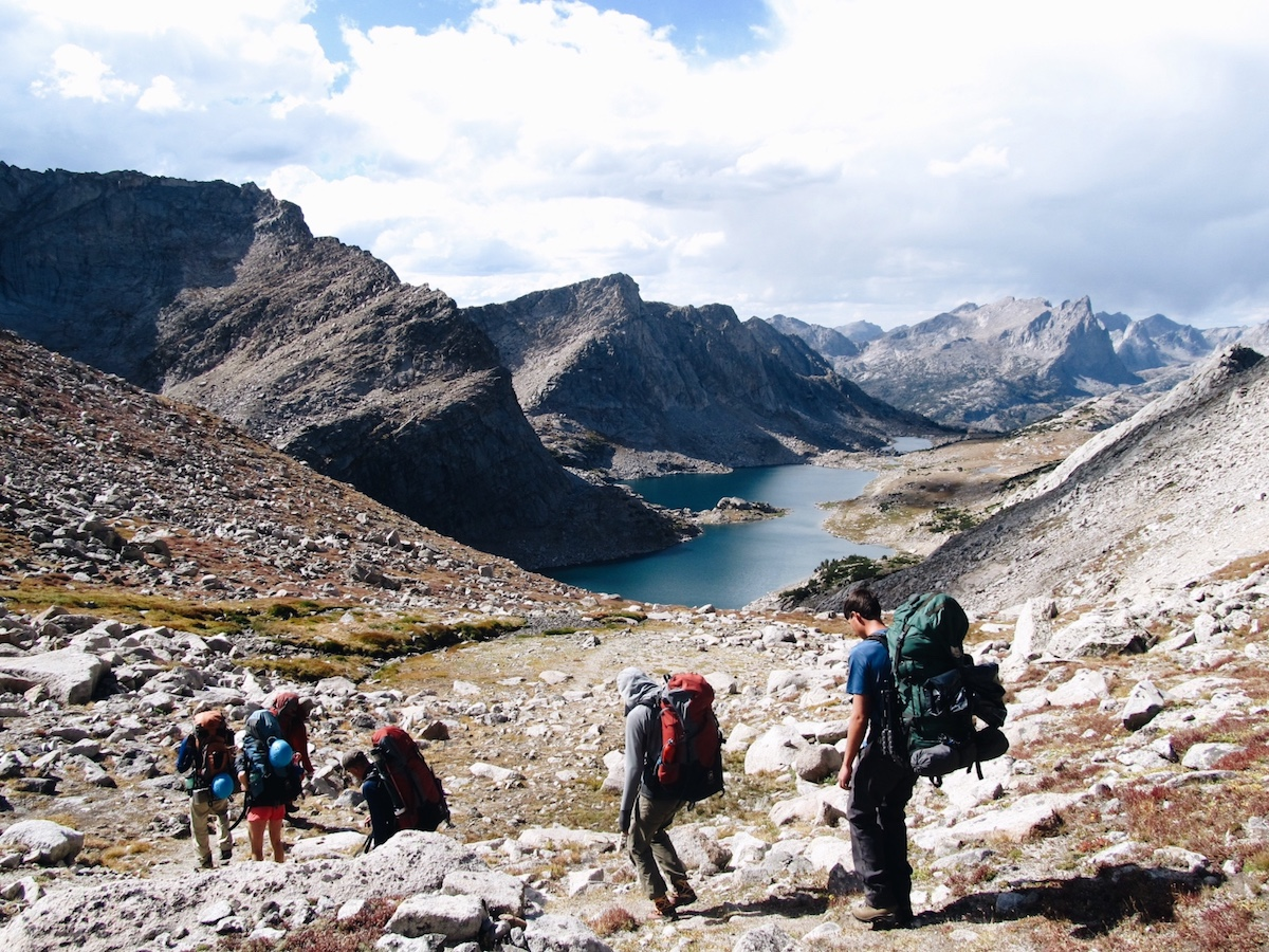 Five NOLS participants hike down rocky slope toward lake in Wyoming's Wind River Range
