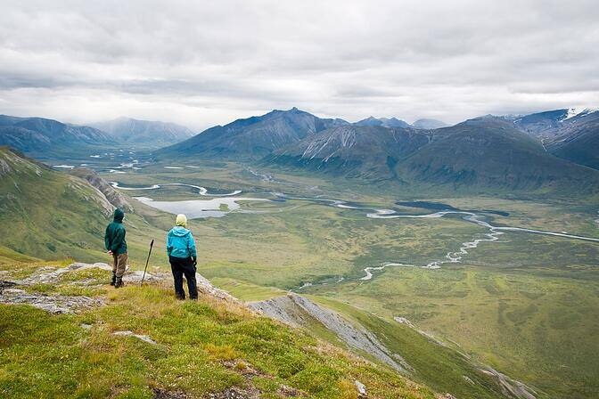 Two people overlook a lush Alaska river valley