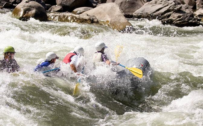 A group of 4 paddles a raft through a rapid